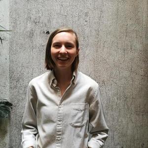 Portrait of Caroline Tracey against a concrete wall